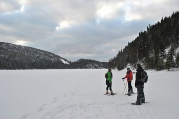 Tracé hivernal d'un sentier qui travers un lac gelé. En été, le tracé contourne le lac - © Mathieu McCann